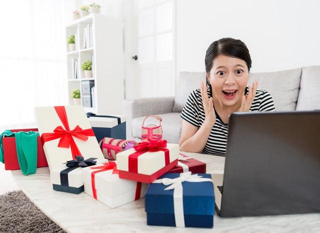 パソコンを見ながら驚く女性と沢山のプレゼント
