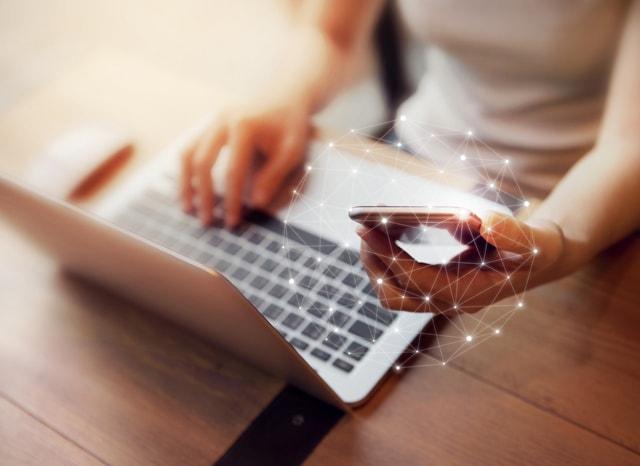 パソコンをしながらネットに繋がったスマホを見る様子