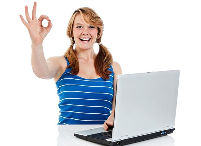 パソコンを開きながらOKサインする女性