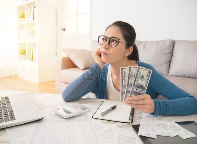 計算しながらお金のことについて考える女性