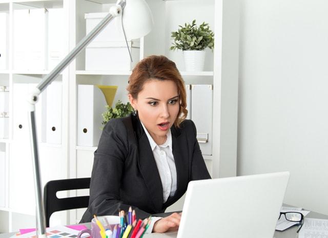 パソコンを見ながら驚く女性