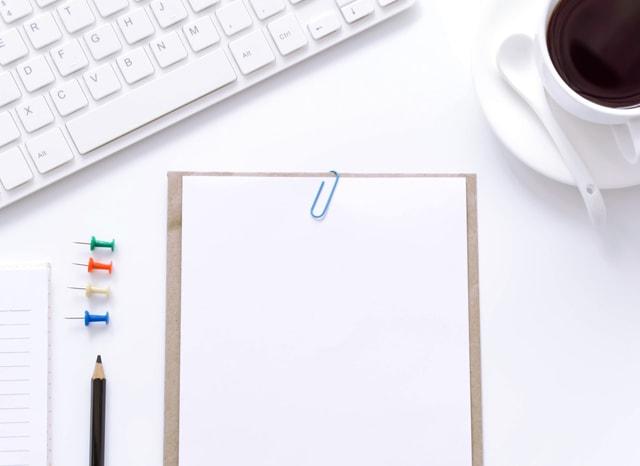 白い机に置かれたパソコンと白紙の紙