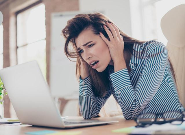 パソコンを見て頭を抱える女性