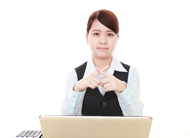 パソコンを開きながら指でバツサインをする女性
