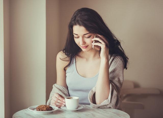 お茶をしながらスマホで電話する女性