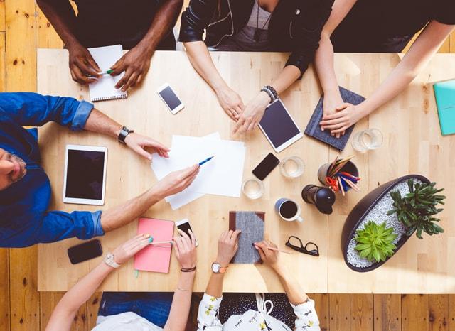 机でスマホやタブレットを使って会議する人々