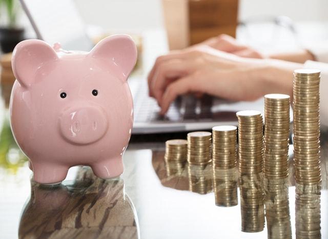 パソコンを触っている人の近くにある豚の貯金箱と積まれた小銭