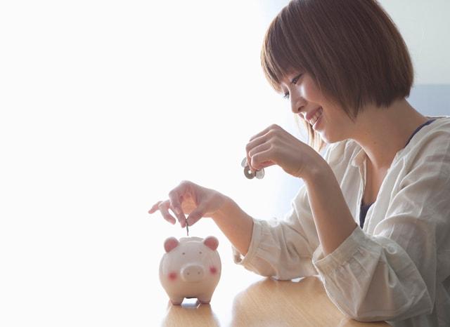 豚の貯金箱に小銭を入れる女性