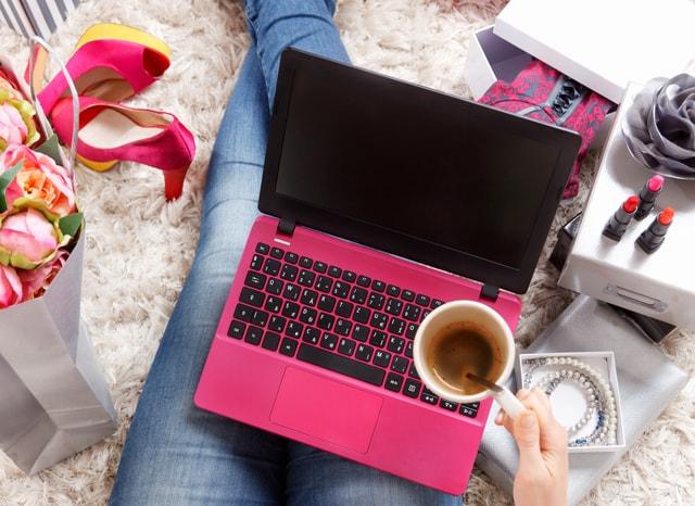 座ってパソコンをする女性の周りに置かれたプレゼント