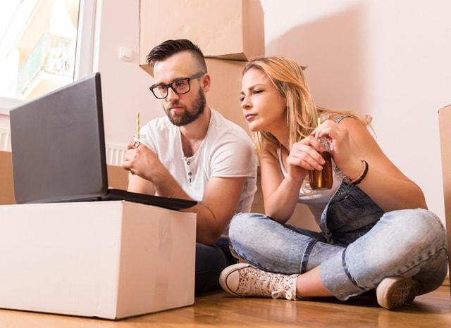 引越し先でパソコンを見ながら考えている夫婦