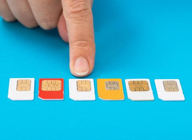 いくつかの並んだSIMカードの中から選んでを指差す人