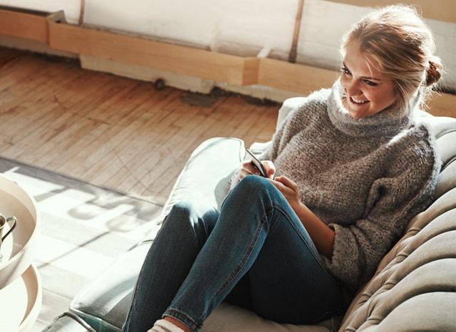 ソファーに座りながら笑顔でスマホを触る女性