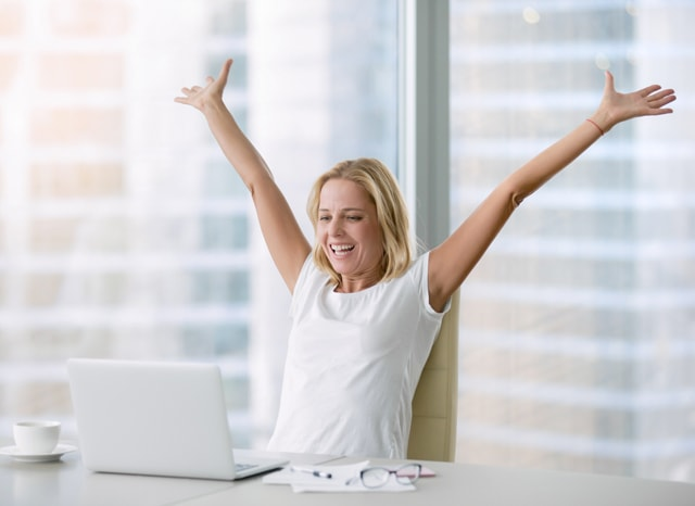 パソコンを見て両手を挙げて喜ぶ女性