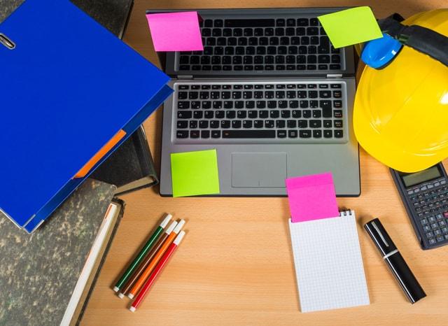 付箋の貼られたパソコンと電卓とヘルメット