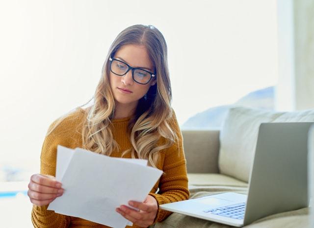 パソコンを開いて資料を見ながら考える女性