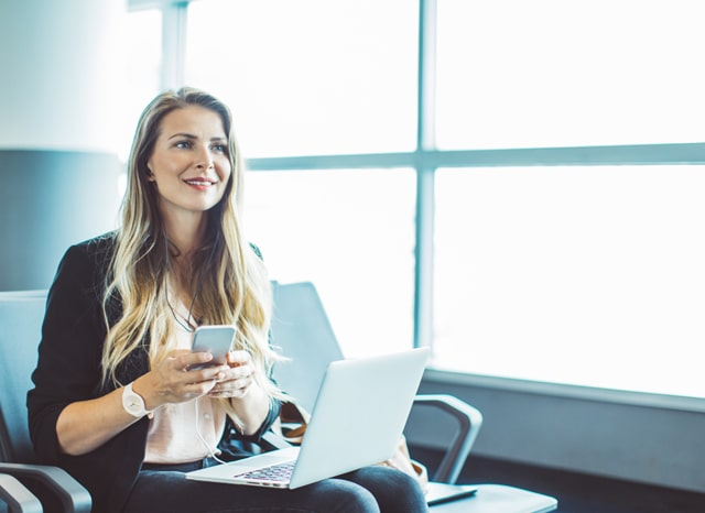 パソコンを開いてスマホを触る女性