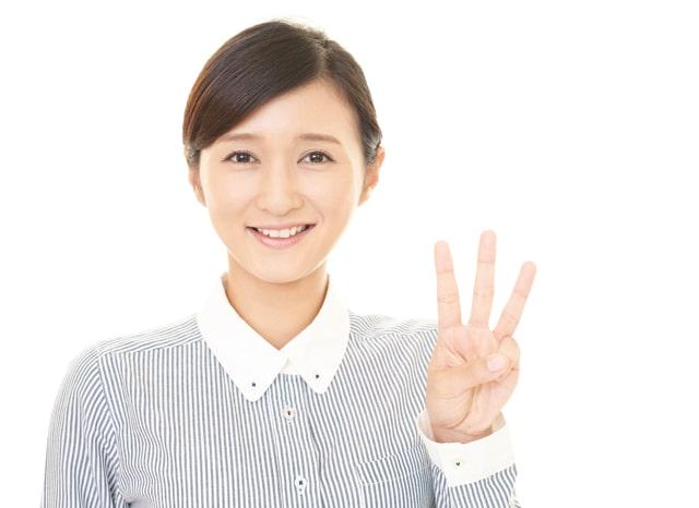 笑顔で指を3本立てる女性