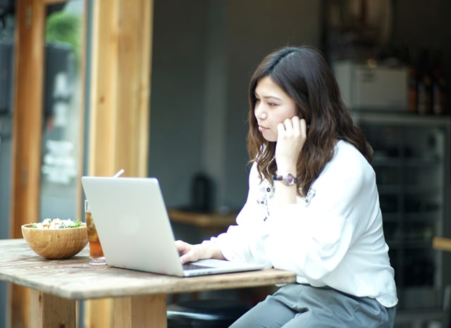 パソコンを触りながら悩む女性