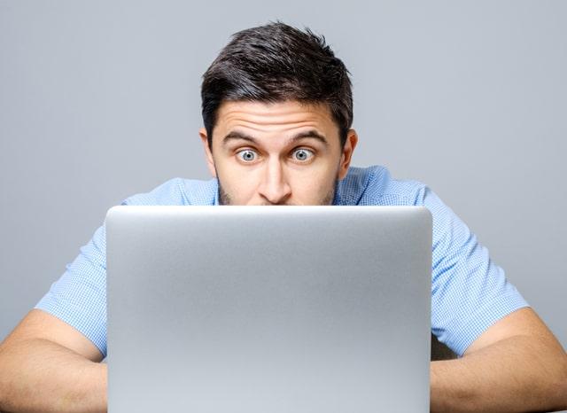 パソコンを見ながら驚いている男性