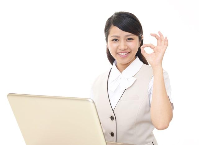 パソコンを使いながらOKサインをする女性