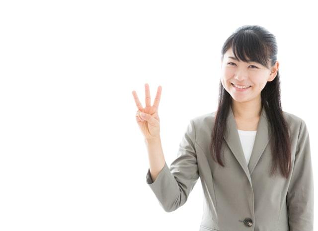 片手で3つを表す笑顔の女性