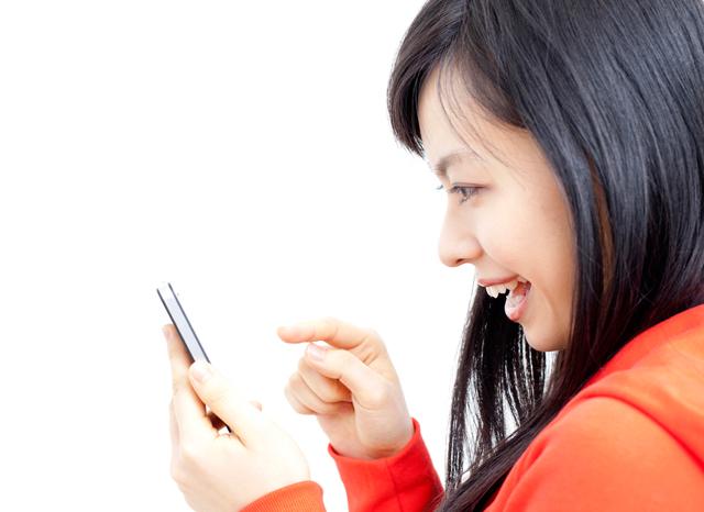 スマホを見ながら笑う女性