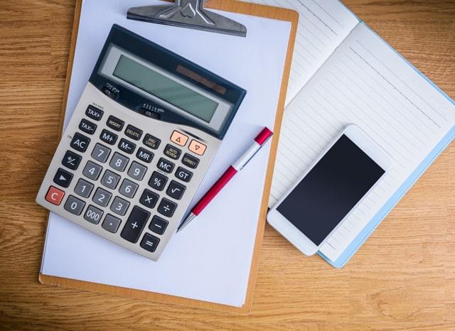 机に置かれたノートと紙と電卓とスマホ