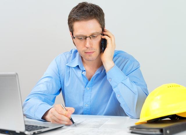 電話をしながらメモを取る建築士の男性