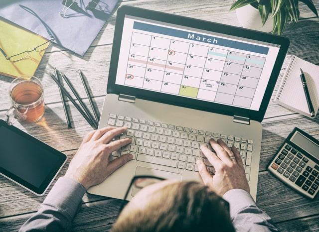 パソコンに写るカレンダーを見る人