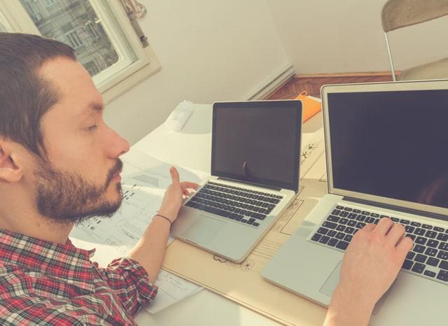 2台のパソコンを触る男性