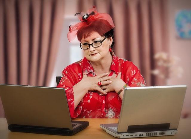 2台のパソコンを広げて見る女性