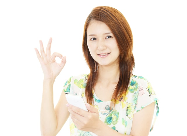 スマホを片手にOKサインする女性
