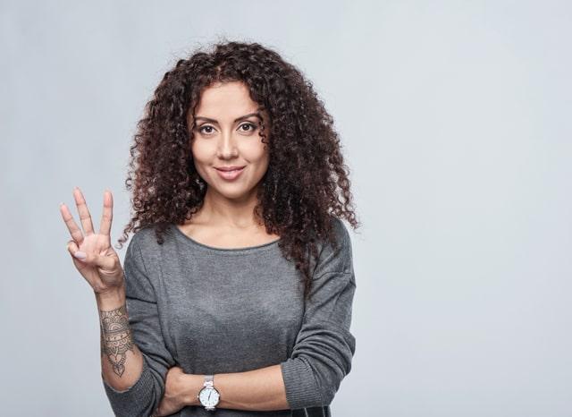 指で3を表す女性