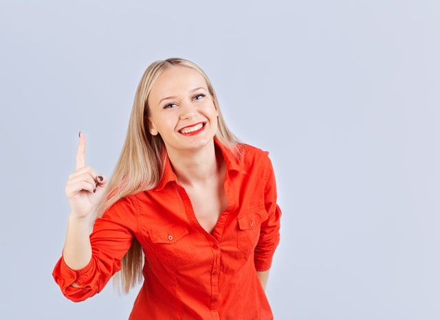 笑顔で人差し指を立てる女性