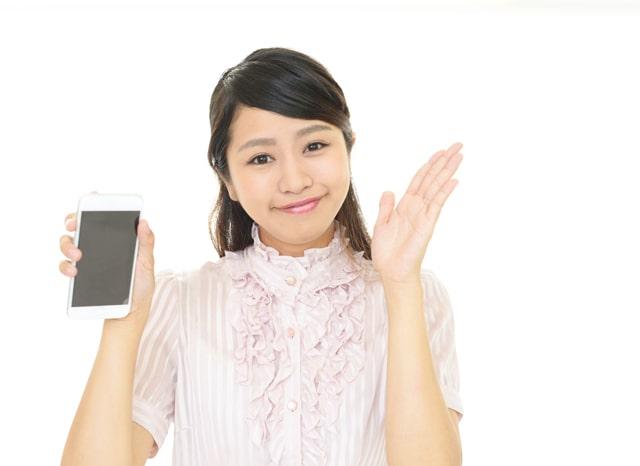 スマホを持ちながら手を上げる女性