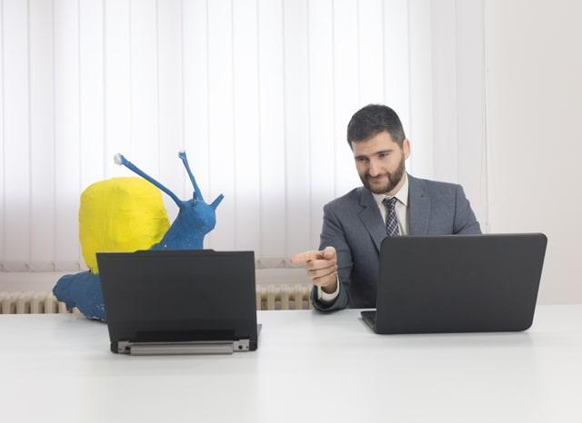 カタツムリの模型があるパソコンを指摘する男性