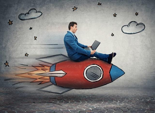描かれたロケットに乗ってパソコンをする男性