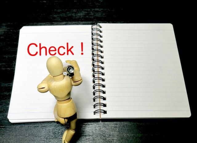 木の人形がペンを持ってCheck!と書く様子
