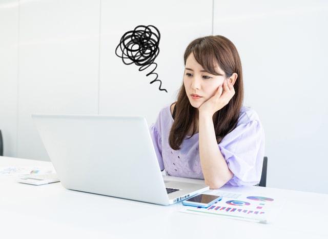 パソコンを見ながら畏まる女性