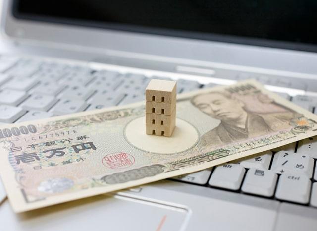 パソコンの上に置かれたお札と建物の模型