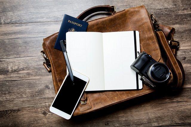 鞄の上にスマホとノートとカメラ