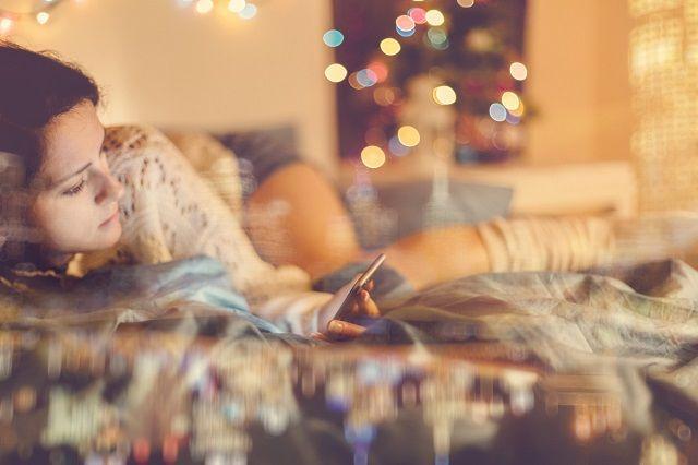 部屋で寝転びながらスマホを見る女性