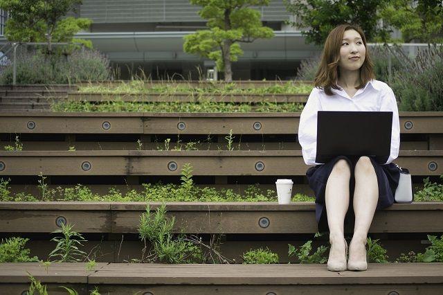 ノートパソコンをひざに乗せベンチに座る女性