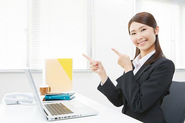 ノートパソコンを前に両手で指差す女性