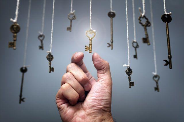 ぶら下がる複数の鍵に触れようとする手