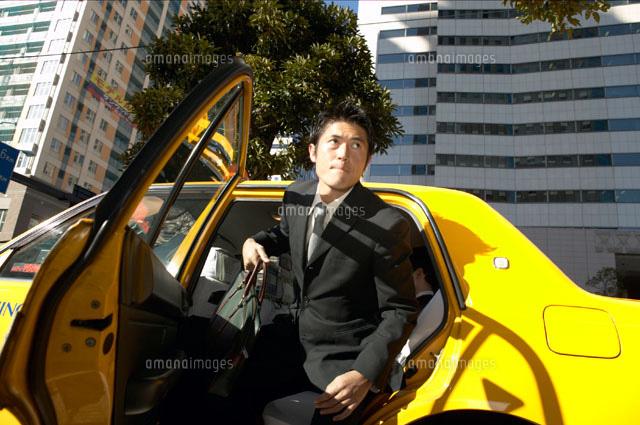 タクシーから降りる日本人ビジネ...