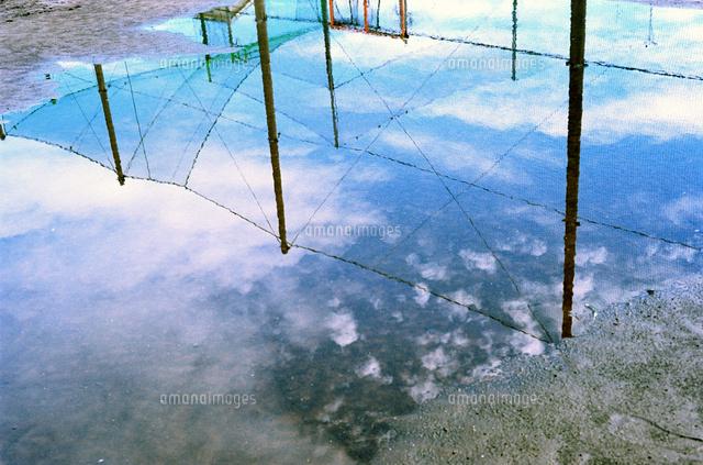 運動公園の水たまりに映る白い雲とネット01143046276の写真素材