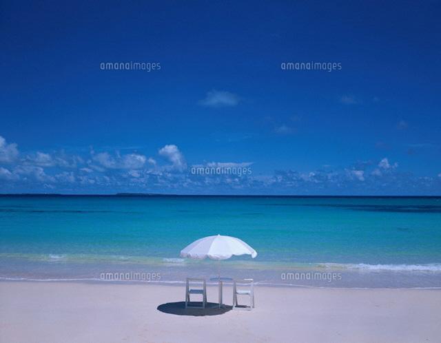 砂浜に白いパラソルとイスのある...