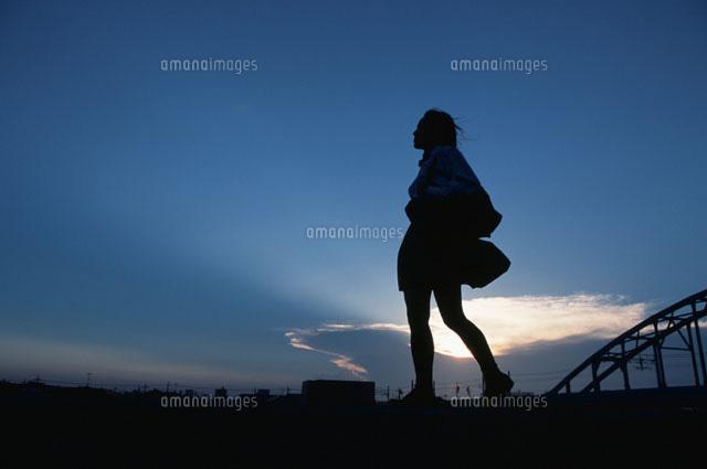 歩く女の子のシルエットと空02208000957の写真素材イラスト素材
