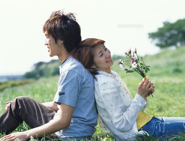 公園でお互いの背中に寄りかかるカップル[02253003926]| 写真素材・ストックフォト・画像・イラスト素材|アマナイメージズ